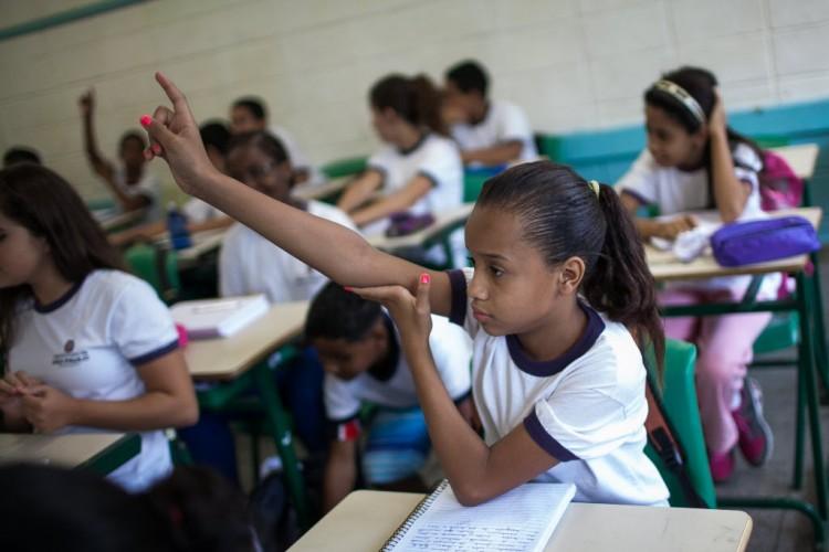 Aluna ergue a mão para perguntar, em aula do sexto ano da escola municipal Frei Damião, na zona sul