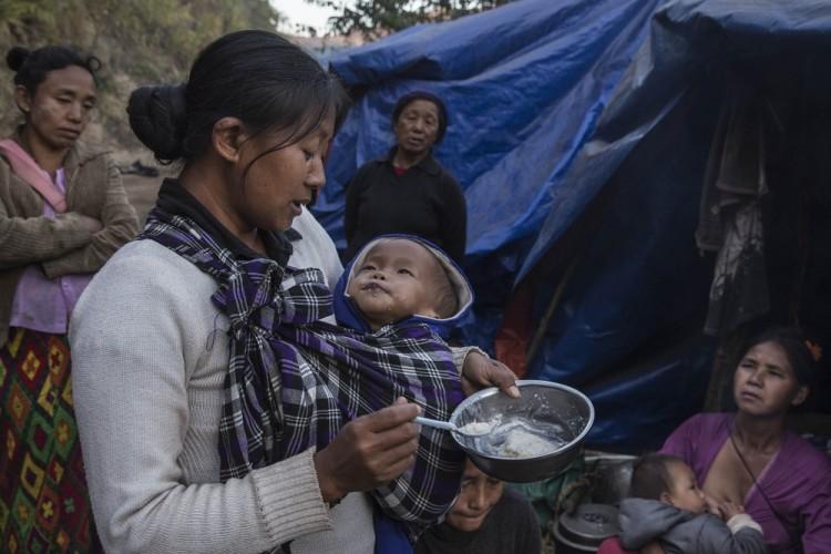 Mulher alimenta bebê em campo de refugiados em Kachin, Myanmar (Foto: AFP)